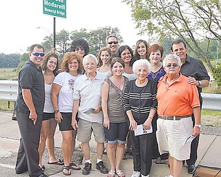 """Members of the Modarelli family stand in front of the new bridge sign after the ribbon-cutting ceremony and dedication of the Dominic """"Dee Dee"""" Modarelli Memorial Bridge in Youngstown. The event also marked the beginning of the Brier Hill Italian Festival."""