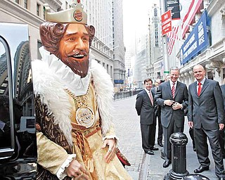 """FILE - In this May 18, 2006 photo, Burger King CEO John W. Chidsey, background center, watches as""""The King"""" mascot of Burger King Corp., arrives at the New York Stock Exchange in New York.  Burger King's spooky """"The King"""" mascot is retiring so the struggling burger chain can refocus its marketing to reach new customers. The mascot has been around for years, but recently has become a more prevalent and somewhat creepy presence in ads.   The fast food chain, which has suffered declining sales, will roll out a new advertising campaign this weekend sans """"The King"""" that will focus on its burgers.    (AP Photo/Richard Drew)"""