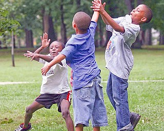 From left, Chris Vancobb, 8, Keondre Lewis, 8, and J'Alfred Clarett, 9, toss a football around at the ENOUGH picnic, an event that brought together families of victims of violent crime.