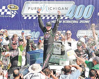 Kyle Busch celebrates his victory in the NASCAR Sprint Cup Series auto race at Michigan International Speedway in Brooklyn, Mich., on Sunday.