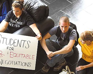 Julie Sabo of Mentor, left, sits quietly with Jim Davis of Columbiana and Christi Walton of Youngstown during a peaceful protest Monday at Youngstown State University.  These three seniors, and other students, had a sit-in at Tod Hall and then walked to Williamson Hall, where contract negotiations with faculty are ongoing. The students are worried about financial aid disbursements, as well as the start of classes.