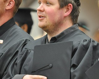 Graduate from the 2011 YSU Summer commencement places his cap above his heart as he begins singing the National Anthem....Photo By:  Lindsay Y McCall | The Vindicator