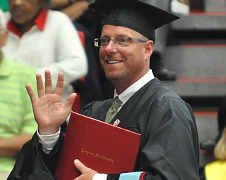 Jason R. Mays waves at his family as he approaches the stage to receive his Masters of Educational Administration degree at the 2011 YSU summer commencement...Photo By:  Lindsay Y McCall | The Vindicator