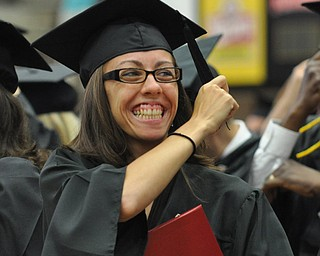 A recent YSU graduate moves her tassle to signify her graduation while smiling at her parents in the crowd...Photo By:  Lindsay Y McCall | The Vindicator