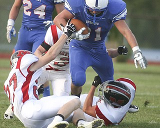 ROBERT  K.  YOSAY  | THE VINDICATOR --..#3 Tommy Marlowe is brought down by a #27  Mathes Ryan Mazey   #3  Craig Hunter  and #50 Chase Ramsey --  Western Reserve Blue Devils  vs Mathews Mustangs at  Western Reserve Stadium Thursday night .--30-..(AP Photo/The Vindicator, Robert K. Yosay)