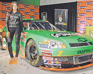 Driver Danica Patrick displays the car that she will drive full-time in the NASCAR Nationwide Series circuit and select Sprint Cup races during an auto racing news conference Thursday, Aug 25, 2011, in Scottsdale, Ariz.  After months of skirting speculation, Patrick announced Thursday that she's leaving IndyCar in 2012 to run a full Nationwide schedule with JR Motorsports and up to 10 Sprint Cup races for Stewart-Haas Racing.  (AP Photo/Paul Connors)