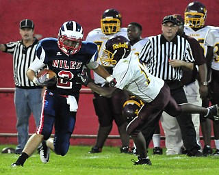 Niles receiver #2Gage McCracken runs upfield after making a catch while John Adams #17 Reginald Thomas tries to tackle him.
