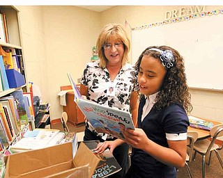 Kiara Pagan, a fourth-grader at Taft Elementary School in Youngstown, checks out some of the new books Laura Sullivan, the school's literacy coordinator, brought for the students. Kiara enjoys reading and says she's happy to be back in school. Monday was the first day of classes for city students.