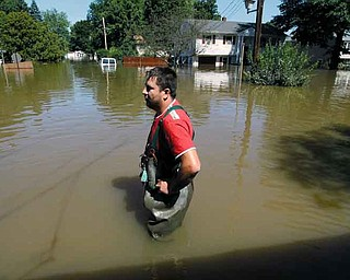 Gino Borova stands in the driveway of his house in Pompton Lakes, N.J., where the Ramapo River crested in the aftermath of Hurricane Irene. Borova has lived in the house for six months and has seen two floods damage his property.