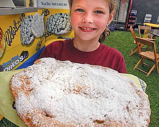 Hannah Heikkinen, 7, of Boardman, enjoys an elephant ear coated in powered sugar during the first day of the Canfield Fair.