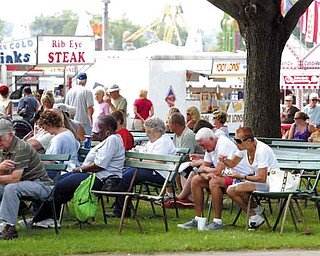 Fairgoers find a shaded area to take a break at the 165th edition of the Canfield Fair, where they can watch others, figure out which concession stand has the best food, or haggle over which attraction to attend. The fair runs today through Labor Day.