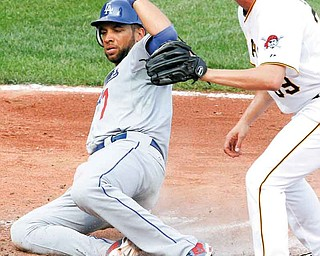 Los Angeles Dodgers' James Loney, left, scores on a wild pitch by Pittsburgh Pirates pitcher Jason Grilli, right, during the seventh inning of a baseball game in Pittsburgh Thursday, Sept. 1, 2011. The Dodgers won 6-4. (AP Photo/Gene Puskar)