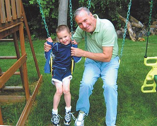 Ron Schutz is playing on the swing set with his grandson, Scottie Eaton, on Father's Day this year. Both live in Canfield.