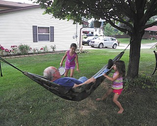 Aliya and Amaya Abeid of New Middletown take turns swinging their Papa Ivan Godoy on the hammock at his home in Campbell.