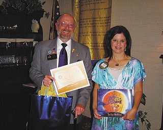 Rotary District Governor W.S. Hays is presented with a certificate by Austintown Rotary President Deanna Spirko for a book donation to Woodside Elementary School library for the Woodside Reads project. Hays visited the club recently and noted Rotary's impact with the Polio Plus drive, which is helping to eradicate polio across the globe. He noted that last year, only 309 cases were recorded throughout the world.