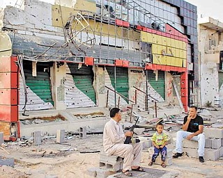 Abdul Basr, 45, center, chats with his neighbor as he sits in front of his damaged pizzeria on Tripoli Street in Misrata, Libya, on Friday.