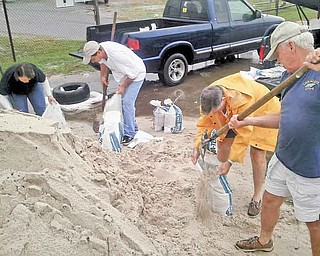James White, right, helps fi ll sandbags with James Lewis at the Harrison County Road Department in Gulfport, Miss., on Friday. Also pictured, from left, Teresa Norman and Glenn Cunningham. Jackson County, one of Mississippi's three coastal counties, declared a state of emergency Friday morning because of a tropical weather system in the Gulf of Mexico.