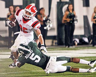 Youngstown State's Jamaine Cook (35) tries to elude Michigan State defender Johnny Adams (5) during the Penguins' season opener Friday in Lansing, Mich. YSU fell to the Spartans, 28-6.
