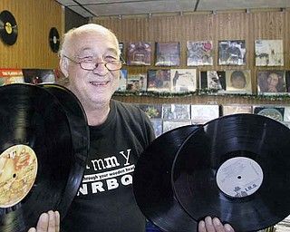 """Underdog Records owner Ron """"Sonny"""" Hrehovcik displays four of the thousands of albums he has in his store. His assortment of records ranges from Frank Sinatra to Ozzy Osbourne."""