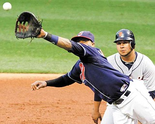 Cleveland Indians first baseman Carlos Santana leaps in front of Detroit Tigers' Jhonny Peralta but can't catch a line drive for an RBI single by Tigers' Don Kelly during the first inning of a baseball game Tuesday, Sept. 6, 2011, in Cleveland. (AP Photo/Mark Duncan)