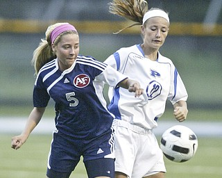 William DLewis  The Vindicator Fitch's MAdison Hefner, left, and Poland's Marissa Trevis go for the ball during Wed action at Poland.