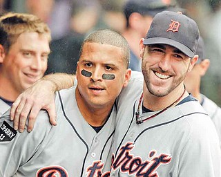 Detroit Tigers starting pitcher Justin Verlander, right, hugs designated hitter Victor Martinez in the dugout after Martinez's grand slam off Cleveland Indians relief pitcher Tony Sipp in the seventh inning of a baseball game Wednesday, Sept. 7, 2011, in Cleveland. (AP Photo/Mark Duncan)