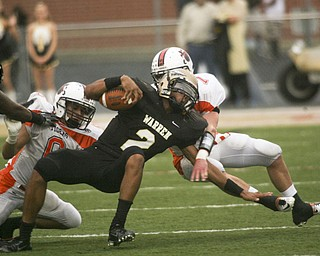 ROBERT  K.  YOSAY  | THE VINDICATOR --..Howlands #7 Zach Wilson and #6  Ken Pozega  Twists down #2 Warren  Jalyn Powell  in the backfield of the first quarter action..Howland Tigers vs Warren G Harding Raiders @ Warren ..--30-..(AP Photo/The Vindicator, Robert K. Yosay)