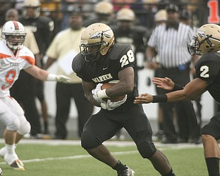 ROBERT  K.  YOSAY  | THE VINDICATOR --..Warren #28 LeShun Daniels takes the hand off from #2  Jalyn Powell  as Howlands #9 Rob Klose looks on.. Le Shun went for 5 yards in first quarter action in Warren..Howland Tigers vs Warren G Harding Raiders @ Warren ..--30-..(AP Photo/The Vindicator, Robert K. Yosay)