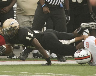 ROBERT  K.  YOSAY  | THE VINDICATOR --..Pushing for more  and the trying for a first down Warrens #11MikQuan Dorsey  #6 Howlands  Ken Pozega  ..Howland Tigers vs Warren G Harding Raiders @ Warren ..--30-..(AP Photo/The Vindicator, Robert K. Yosay)