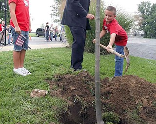 Boardman police officer Bill Woods and his children, Elena, left, and Jacob, plant a red maple tree at Stadium Drive Elementary School in Boardman as part of a Sept. 11 commemoration. Elena, a second-grader, and Jacob, a third-grader, were among the Boardman students, police, firefighters and the Boardman Band who planted trees and placed flags to mark the event.