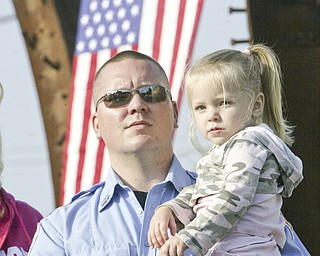 William D. Lewis | The Vindicator Austintown Fire Fighter Nick Reed holds his daughter Ariana, 3, during a Sunday observance of the 9/11 attacks at the Austintown 9/11 Memorial Park. Hundreds of area residents and representatives from many fire departments where on hand for the event.