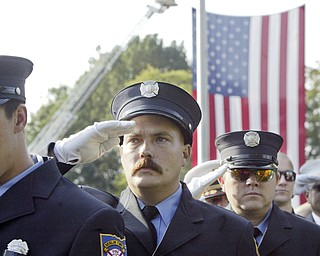 William D. Lewis | The Vindicator Jackson Twp Fire Dept.Randy Wilson Jr. salutes during a Sunday observance of the 9/11 attacks at the Austintown 9/11 Memorial Park. Hundreds of area residents and representatives from many fire departments where on hand for the event.
