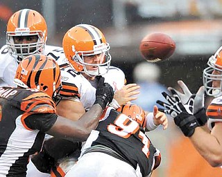 Cleveland Browns quarterback Colt McCoy throws an incomplete pass while pressured by Cincinnati Bengals defensive end Carlos Dunlap, front left, and Robert Geathers in an NFL football game on Sunday, Sept. 11, 2011, in Cleveland. Reaching for the ball is Cleveland Browns center Alex Mack. (AP Photo/David Richard)
