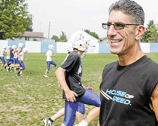 Lisbon football coach Jim Tsilimos watches his Blue Devils practice Wednesday. Tsilimos loved his time off the field as a football parent, but is happy to be back coaching at Lisbon, which has been his home since 1990.