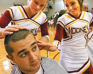 Carmen Lanzo has his hair clipped by his sister, Kiersten Lanzo, and Eva Colwell at a rally Thursday for the Mooney football team. The rally also was designed to show solidarity with Mooney senior Dante DelSignore who has battled cancer for four years and is receiving his fourth round of chemotherapy in his battle against osteosarcoma.