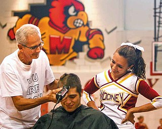 Nick Colla and Callie Tofi l clip Austin Trgovicich's hair at a rally for the football team and for student Dante DelSignore who has battled cancer for four years.