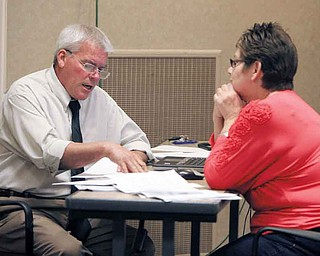 Eloisa Luminiello of Austintown consults with Ken Jones, an appraiser with Integrity Appraisal Services Inc. of Niles, concerning the tentative valuation of her property at Mahoning County's reappraisal information center at Oakhill Renaissance Place, Youngstown. The consultations continue through Oct. 7.