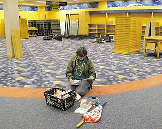 FILE - In this Sept. 15, 2011 file photo, Sue Schmidt of Shaker Heights, Ohio, sits on the floor to sort through her potential purchases in a nearly-empty Borders bookstore in Solon, Ohio. This Borders store was scheduled to close its doors for good at the end of the day. (AP Photo/Amy Sancetta, File)