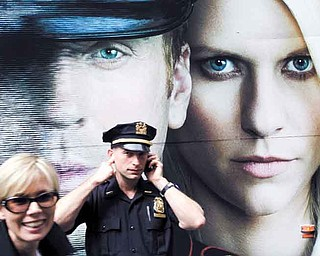 """A police officer covers his ears to block out noise from demonstrators gathering to call for the occupation of Wall Street, Saturday, Sept. 17, 2011, in New York. According to their website, the mission of the leaderless resistance movement is to flood thousands of people into lower Manhattan, set up beds, kitchens, peaceful barricades and occupy Wall Street for a few months in order to persuade President Barack Obama to establish a commission to end """"the influence money has over representatives in Washington."""" (AP Photo/Frank Franklin II)"""