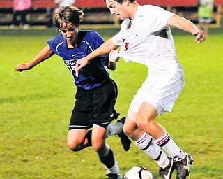 Cuyahoga Valley  Christian Academy's Zach Bosshard, left, grabs Cardinal Mooney soccer player Pat Price during Tuesday's 1-1 tie in Struthers.
