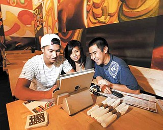 Taylor Minatogawa, right, watches his friends Reanne Lamason and Kyerin Cubos navigate the iPad ordering system at Stacked in Torrance, California on September 10, 2011.  (Liz O. Baylen/Los Angeles Times/MCT)