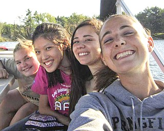 """Enjoying a boat ride and some fun at a get-acquainted meeting Aug. 28 at Lake Milton were, from left, Kayla Windsor, an AFS host sister; Paticha """"Pie"""" Areepipatkul from Thailand; Catalina Rojas Rodriguez from Chile; and Sarah Gabrick, another AFS host sister."""