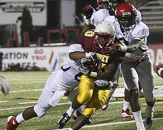JESSICA M. KANALAS | THE VINDICATOR ..Mooney's junior running back Justus Ellis-Moore fights off the Red Lion Christian Academy's defense during the first quarter of Saturday night's game at YSU stadium. ..-30