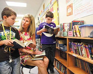 Language-arts teacher Shelly Culp helps fifth-graders Conner Murphy, left, and Matt Bohr select books from some of the new books she purchased with a grant. The Frank Ohl Intermediate teacher applied for and received a $2,912 grant from the Martha Holden Jennings Foundation.