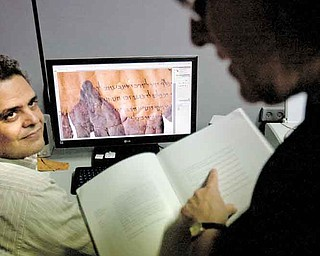 Photographer Yair Medina, left, shows Pnina Shor, right, curator and Head of Dead Sea Scrolls Project at the Israel Antiquities Authority, IAA, scanned fragments of the Dead Sea Scrolls on a computer screen, at the IAA offices at the Israel Museum in Jerusalem, Monday, Sept. 26, 2011. Two thousand years after they were written and decades after they were found in desert caves, some of the world-famous Dead Sea Scrolls are available online. Israel's national museum and the international web giant Google are behind the project, which saw five scrolls go online Monday. (AP Photo/Sebastian Scheiner)