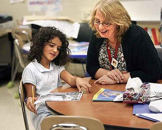 Cerise Mills, a third grade teacher at Taft Elementary School in Youngstown, works with third grader Delaney Niemczura on her lessons.