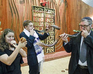 Rabbi Joseph Schonberger of Temple El Emeth in Liberty leads the sounding of the shofar (ram's horn) during a practice session with Meryl Schor, 14, left, and Korey Burdman, 15. The traditional sounding of the ram's horn will be part of High Holiday services. Rosh Hashanah begins at sundown tonight.