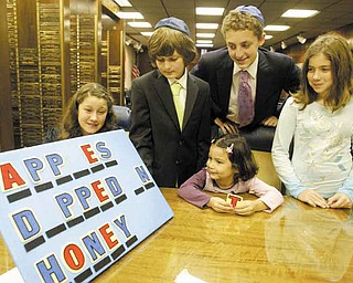 """Elyse Silverman devised a """"Wheel of Fortune""""-style game for youth at Temple El Emeth. """"Apples dipped in honey"""" relates to the traditional foods eaten at Rosh Hashanah to ensure a """"sweet"""" new year. Guessing the phrase are, from left, Meryl Schor, Taylor Burdman, Korey Burdman, Ariella Westreich and Sophie Alpert."""