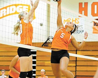 Mineral Ridge's Lea Whitmer (5) tries to make a play after Springfield's Morgan Buchenic, sends the volleyball onto the Mineral Ridge side during Tuesday's match at Mineral Ridge High. The Tigers won in three games.