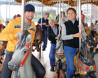 Troy Reinhart, left, 39, of Manhattan, and his parents Sandra Reinhart, right, 69, and Robert Reinhart, back right, 77, both of Girard, paid a visit to Jane's Carousel at Brooklyn Bridge Park. The carousel, which reopened in New York on Sept. 16, was restored by Jane Walentas who purchased it in 1984 from Idora Park.